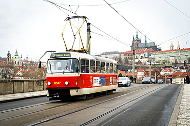 A traditional red tram crosses Manesuv most (bridge) with St. Vitus Cathedral and Prague Castle in the background, Prague, Czech Republic, Europe