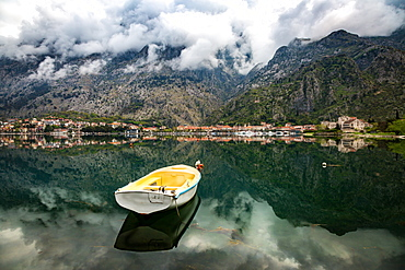 A small fishing boat sits in the reflection of the Old Town (stari grad) of Kotor in Kotor Bay, UNESCO World Heritage Site, Montenegro, Europe