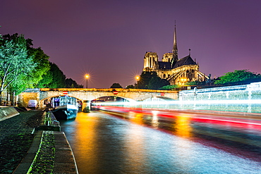 Long exposure of a boat on the River Seine passing Notre Dame Cathedral on a wet evening in Paris, France, Europe