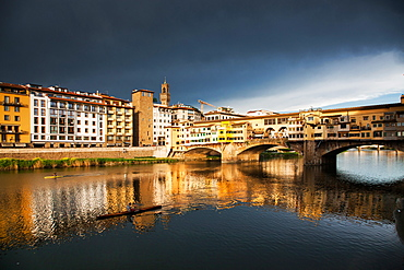 Ponte Vecchio reflected in the Arno River against a dark blue stormy sky, Florence, UNESCO World Heritage Site, Tuscany, Italy, Europe