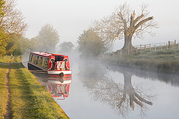 Barge (longboat) (narrowboat) moored on the Leeds Liverpool Canal in misty conditions shortly after sunrise near Skipton, North Yorkshire, Yorkshire, England, United Kingdom, Europe