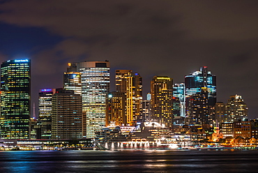 Large cruise ship docked at International Terminal in Sydney harbour after dark with city skyline, Sydney, New South Wales, Australia, Pacific