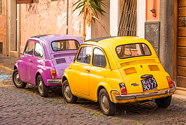 Two vintage Fiat 500s with Roma number plates parked in colourful backstreet of Trastevere, Lazio, Italy, Europe