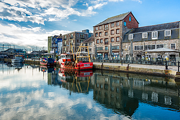 Fishing boats moored at Sutton harbour, with shops and cafes on the quayside, The Barbican, Plymouth, Devon, England, United Kingdom, Europe