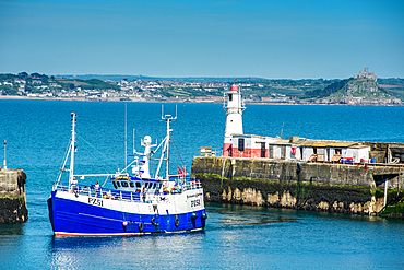 Fishing boat coming into the harbour at the village of Newlyn with St. Michael's Mount at Marazion in the distance, Cornwall, England, United Kingdom, Europe