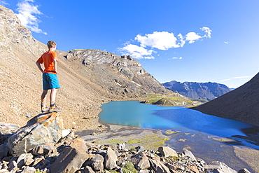 A boy looks at Lai da Fasch'Alba from above, Val Tasna, Engadine Valley, Graubunden, Switzerland, Europe