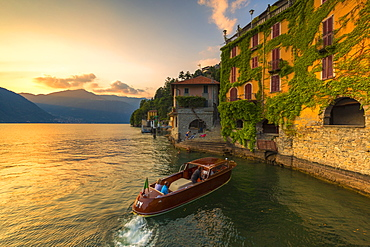 A boat of tourists stops to observe the sunset, Nesso, Province of Como, Lake Como, Italian Lakes, Lombardy, Italy, Europe