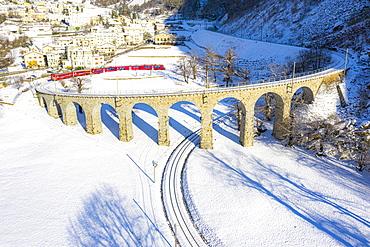 Bernina Express passes over the helical (spiral) viaduct of Brusio, UNESCO World Heritage Site, Valposchiavo, Canton of Graubunden, Switzerland, Europe
