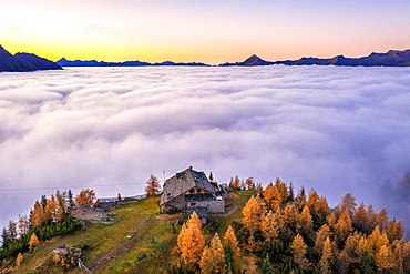 Fog covers the Valmalenco (Val Malenco) with the mountain range of Disgrazia illuminated by sunrise in the background and the Motta mountain hut in the foreground, Valtellina, Lombardy, Italy, Europe
