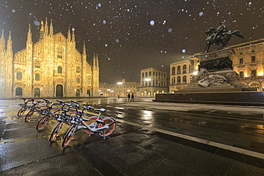 Parked bicycles in Piazza Duomo during a night snowfall, Milan, Lombardy, Northern Italy, Italy, Europe