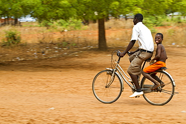 A school boy gets a lift home on the back of a bicycle, Ghana, West Africa, Africa