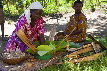 A woman wraps some groundnuts in a banana leaf, Uganda, Africa