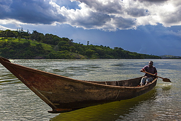 A man paddles a wooden dugout canoe at the source of the River Nile in Uganda, Africa