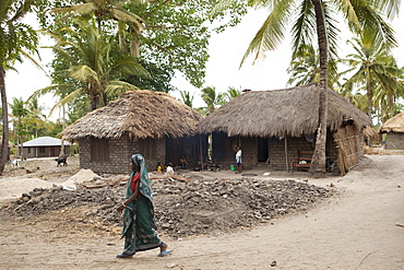 A woman walks past a traditional mud hut home with a solar panel on the top of it, Tanzania, East Africa, Africa