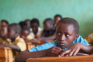 A school girl glances up to read the blackboard, Rwanda, Africa