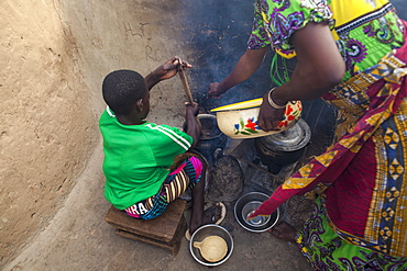A young girl helping her mother cook at their home in Tinguri, Ghana, West Africa, Africa - 1270-144