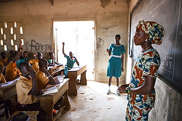 A female teacher teaching at the front of the classroom at a primary school in Ghana, West Africa, Africa