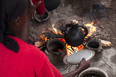A woman fans the open fire as she makes coffee in a traditional Ethiopian coffee pot, Ethiopia, Africa