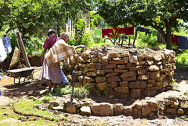 A couple help each other to build a keyhole garden, Lesotho, Africa
