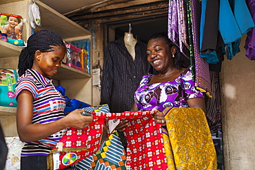 A female shopkeeper showing different colourful materials to a potential customer, Nigeria, West Africa, Africa