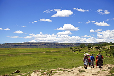 A group of woman walking through the rural countryside of Lesotho under a big blue sky, Lesotho, Africa