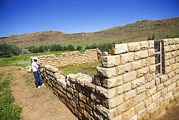 A man building a house out of stone, Lesotho, Africa