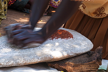 A woman using two stones to grind grain in to flour, Uganda, Africa