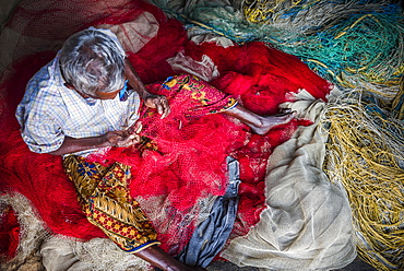 Fisherman mending net at Kappil Beach, Varkala, Kerala, India, Asia