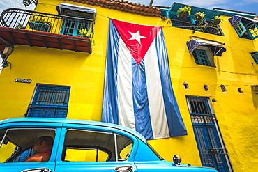 Old American classic car and huge Cuban flag on yellow building in Havana, La Habana (Havana), Cuba, West Indies, Caribbean, Central America