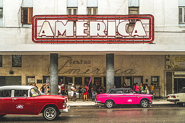 Pink and red vintage cars outside Teatro America in rain, La Habana (Havana), Cuba, West Indies, Caribbean, Central America
