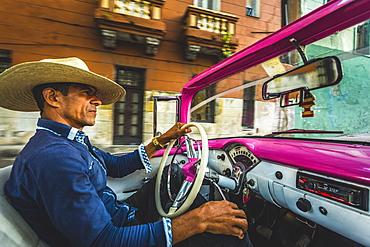 Local classic car driver at sunset in La Habana, Havana, Cuba, West Indies, Caribbean, Central America