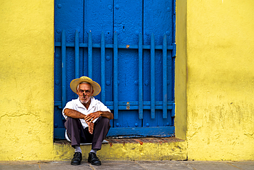 An elderly Cuban sitting on a doorstep, smoking a cigar, Trinidad, Sancti Spiritus Province, Cuba, West Indies, Caribbean, Central America