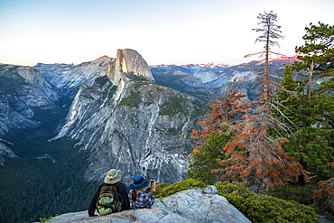 A couple takes a break at Glacier Point to look at Half Dome in Yosemite National Park, UNESCO World Heritage Site, California, United States of America, North America