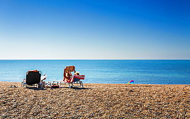 People relaxing on deckchairs on the beach, Brighton, East Sussex, England, United Kingdom, Europe