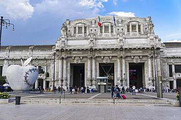 Milan Railway station facade with artwork of The Reintegraded Apple sculpture outside Milano Centrale at Piazza Duca dAosta, Milan, Lombardy, Italy, Europe