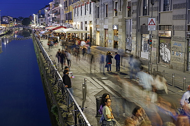 Navigli district at night with crowd on the banks of Naviglio Grande Canal, Milan, Lombardy, Italy, Europe