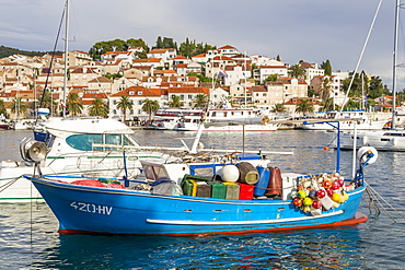 Colorful boat anchoring in the port of Hvar Town with view to the old town in the background, Hvar, Croatia, Europe