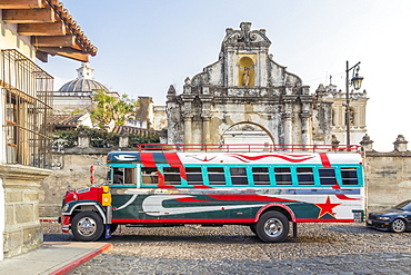 A typical colorful painted chicken bus passing at the entrance gate of San Francisco Church in Antigua, UNESCO World Heritage Site, Guatemala, Central America