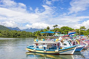 Colorful tour boats anchoring at the port of Paraty with view to the Serra da Bocaina mountain range, Rio de Janeiro, Brazil, South America