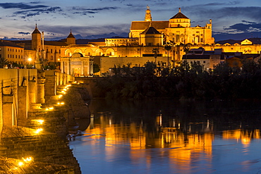 The illuminated Mosque-Cathedral (Great Mosque of Cordoba) (Mezquita) and the Roman Bridge at dusk, UNESCO World Heritage Site, Cordoba, Andalusia, Spain, Europe