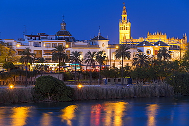 The Giralda Bell Tower and Plaza de Toros seen from the banks of Guadalquivir River at dusk, Seville, Andalusia, Spain, Europe