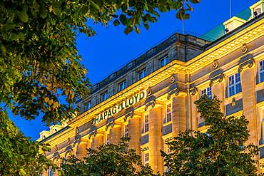 The illuminated Hapag-Lloyd building at the Inner Alster in Hamburg at dusk