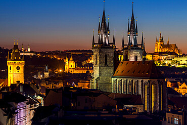 View to Our Lady before Tyn Church, the Old Town Hall Clock Tower and Prague Castle at dusk, Prague, Bohemia, Czech Republic