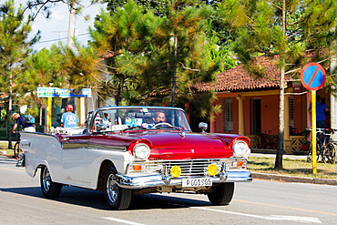 Red and White convertible vintage taxi on main road in Vinales, UNESCO World Heritage Site, Cuba, West Indies, Caribbean