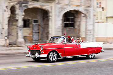 Red and white vintage American taxi driving along the Malecon, Havana, Cuba, West Indies, Caribbean