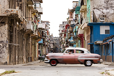 A vintage American car driving across a street in Havana, Cuba, West Indies, Caribbean, Central America