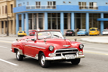 A red convertible vintage American car driving along the Malecon in Havana, Cuba, West Indies, Caribbean, Central America