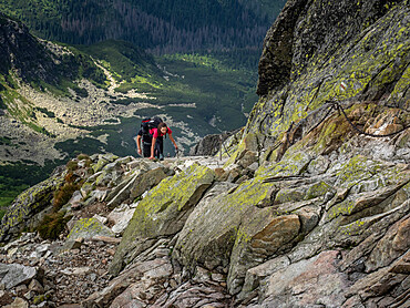 Lady scrambling on Swinica, 2301m, on the Polish/Slovak border in the Tatra mountains assisted by metal chains in some sections