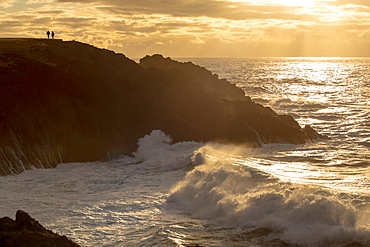 A couple enjoy the view of sunset and crashing waves, Newport, Oregon, United States of America