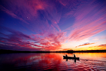 Two paddlers in a canoe on a lake at sunset, Ely, Minnesota, United States of America